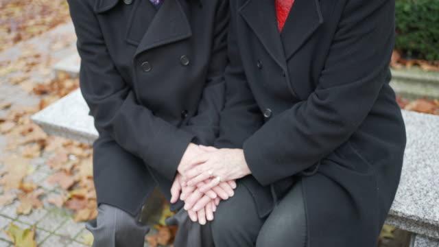 ein älteres ehepaar, das zusammen sitzt und sich gegenseitig die hände hält - real wife sharing stock-videos und b-roll-filmmaterial