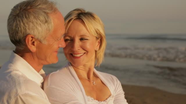 vidéos et rushes de senior couple sitting together on beach - vue latérale