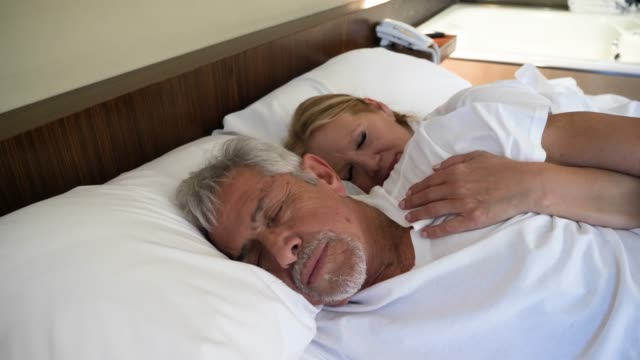 Senior couple sleeping very tranquil and woman cuddling from behind her partner