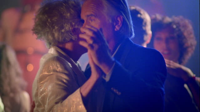 ms senior couple slow dancing, smiling + talking on dance floor in nightclub - coppia di età matura video stock e b–roll