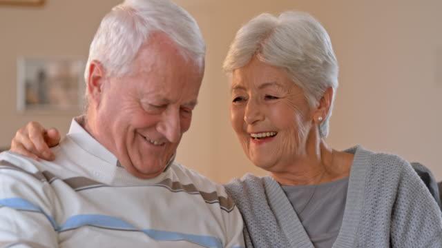 slo-mo-senior paar lächelnd, als sie auf sofa - teil einer serie stock-videos und b-roll-filmmaterial
