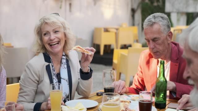 stockvideo's en b-roll-footage met hoger paar dat bij elkaar over dranken en pizza glimlacht - 70 79 jaar