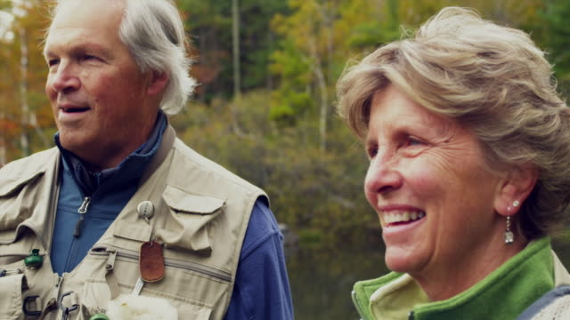 CU Senior couple smiling, standing and looking at lake, Manchester, Vermont, USA