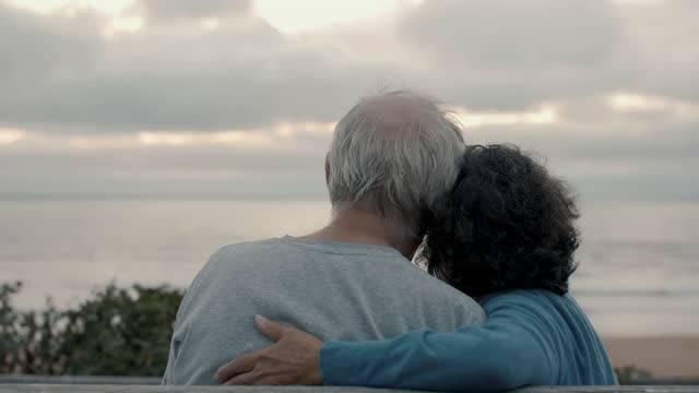 senior couple snuggling watching sunset at beach - husband stock videos & royalty-free footage