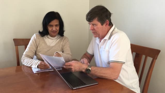 Senior couple sort their financial bills on a laptop