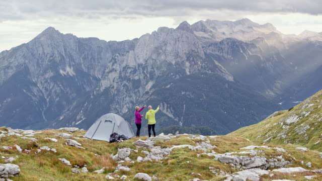 DS Senior couple standing next to their tent on a high mountain meadow and talking about the view