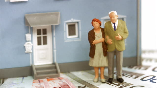 senior couple standing on bills in front of a house. - figurine stock videos and b-roll footage