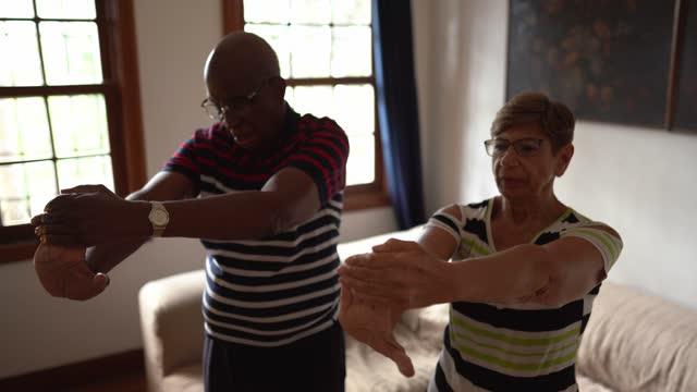 vídeos de stock, filmes e b-roll de casal de idosos se alongando em casa - braço humano