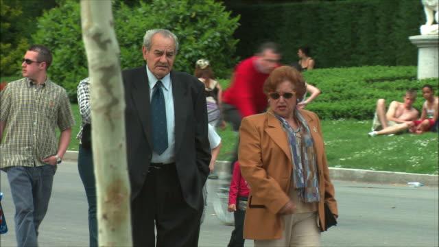 ws pan senior couple strolling in retiro park, madrid, spain - three quarter length stock videos & royalty-free footage