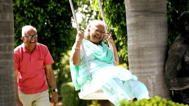 Senior couple swinging in the park, Delhi, India