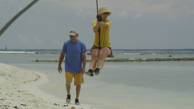 senior couple swinging on the beach - isola di tahaa video stock e b–roll