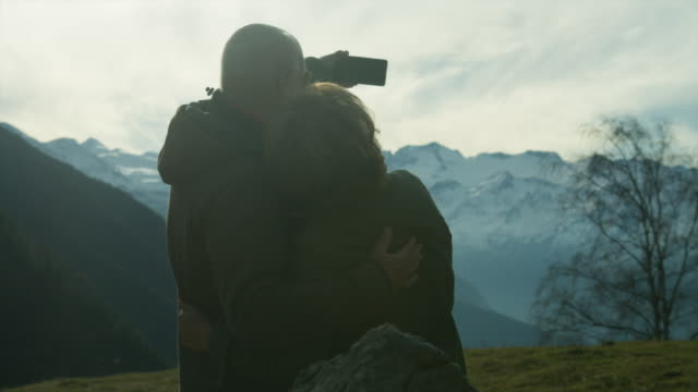 Senior couple taking a selfie and kissing each other surrounded by mountains.