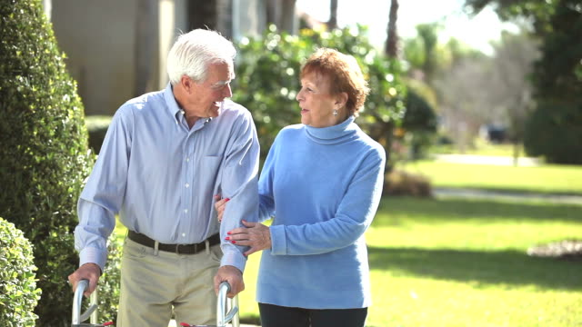senior couple taking a walk, man using walker - arm in arm stock videos and b-roll footage