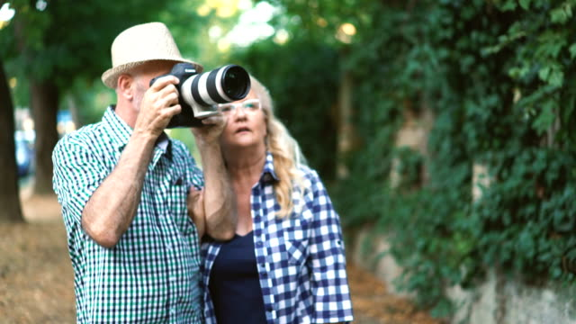 senior couple taking photos of nature. - telephoto lens stock videos and b-roll footage