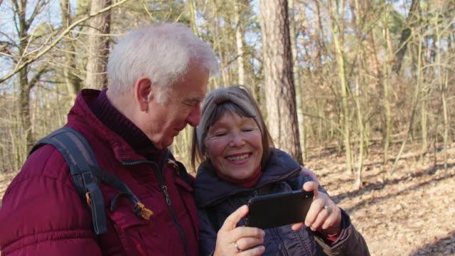 seniorenpaar, das sich in wanderreise selbst porträtiert - fotografieren stock-videos und b-roll-filmmaterial