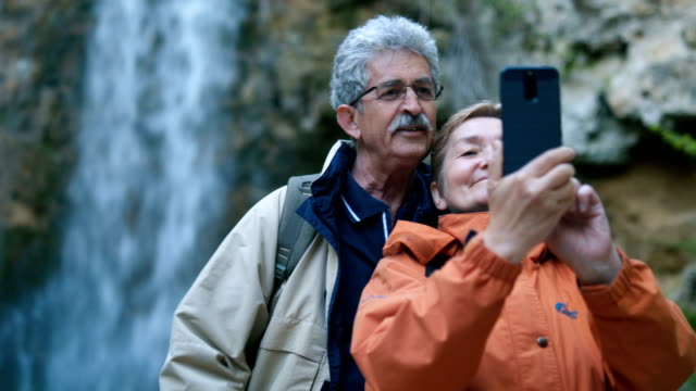 senior couple taking selfie by the waterfall - senior couple stock videos & royalty-free footage