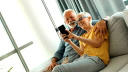 Senior couple taking selfies at home.