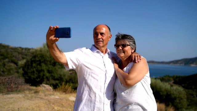 stockvideo's en b-roll-footage met senior paar nemen selfies aan de kust - zelfportret fotograferen