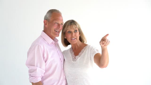vídeos de stock e filmes b-roll de senior couple talking about something and pointing somewhere - carinhoso