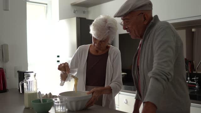 vídeos de stock, filmes e b-roll de casal sênior conversando e cozinhando juntos em casa - jovem de espírito