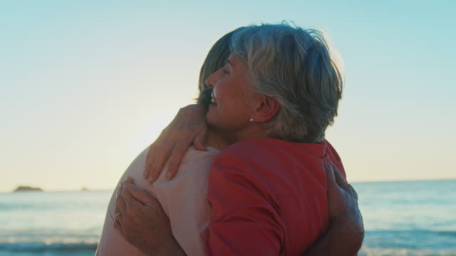 Senior couple talking and embracing at beach