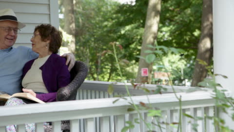senior couple talking and reading on porch - porch stock videos & royalty-free footage