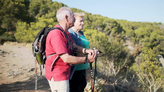 senior couple talking and resting while hiking outdoors. - hiking pole stock videos & royalty-free footage
