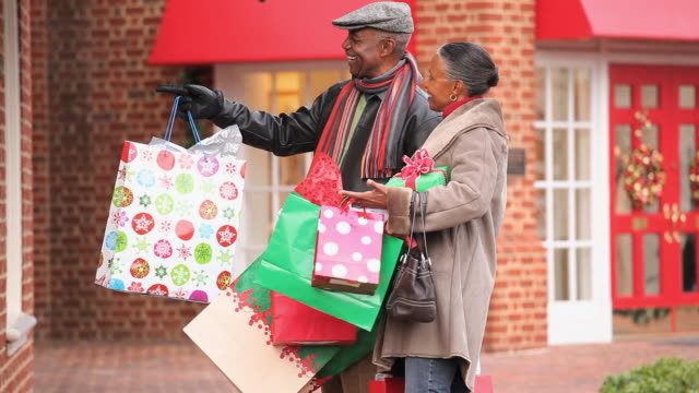 vídeos y material grabado en eventos de stock de ms tu senior couple talking and smiling, carrying shopping bags on sidewalk / richmond, virginia, usa - sobretodo