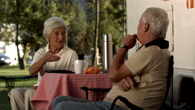 hd: senior couple talking at the campsite - camper van stock videos & royalty-free footage