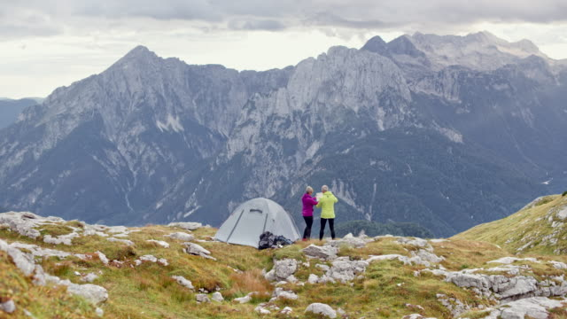 DS Senior couple talking by their tent on a mountain meadow and holding a map
