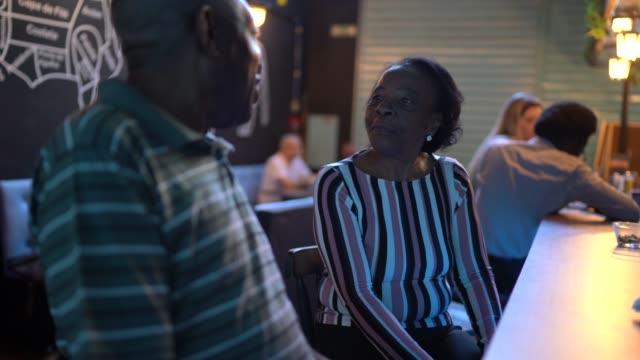 senior couple talking in a bar - flirting stock videos & royalty-free footage