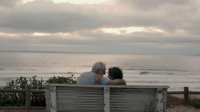 vídeos de stock e filmes b-roll de senior couple talking, kissing, laughing on bench by sea - banco assento