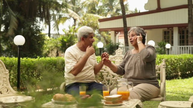Senior couple talking on a mobile phone in a lawn