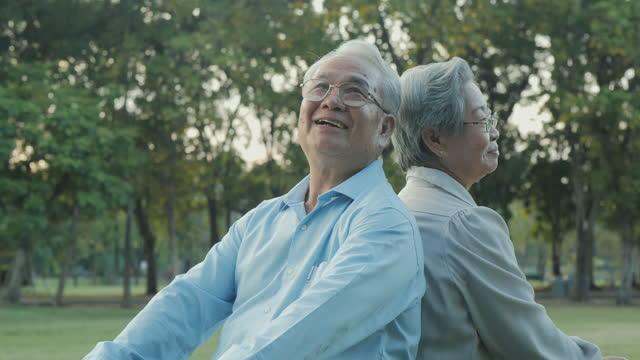 庭で一緒に話すシニアカップル。彼らは笑顔で面白い話をする。 - 年の差カップル点の映像素材/bロール