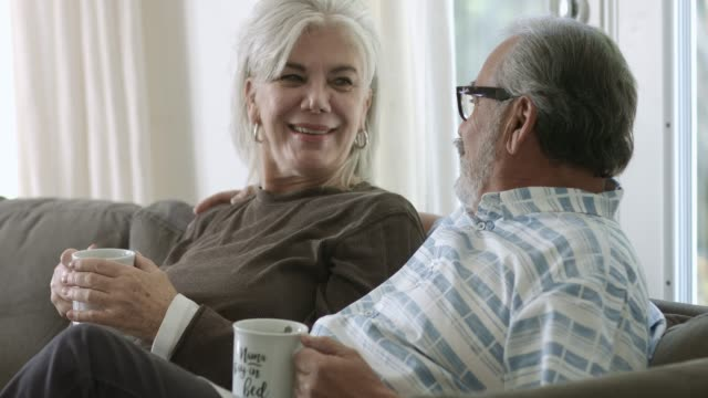 senior couple talking while having coffee at home - tre quarti video stock e b–roll