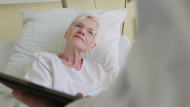 vídeos de stock e filmes b-roll de senior couple talking with doctor in hospital ward - visita