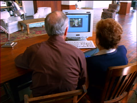 REAR VIEW senior couple teleconferencing with young woman computer screen in apartment