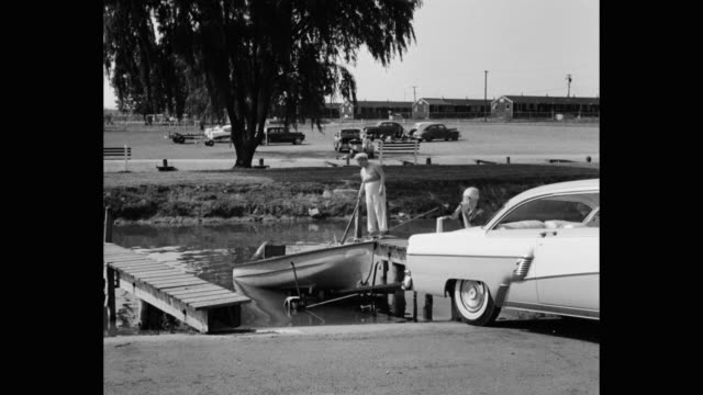 senior couple towing motorboat out of water onto trailer with pulley - loch stock videos & royalty-free footage