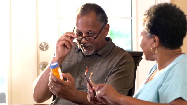 Senior couple trying to read prescription bottle label