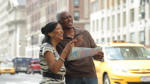 A senior couple use a map to recognize landmarks in New York City.