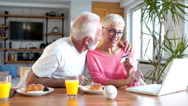 vidéos et rushes de couple de personnes âgées en utilisant une carte de crédit pour magasiner en ligne - 60 64 ans
