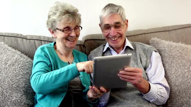 coppia senior utilizzando la tavoletta digitale a casa. - organizzatore elettronico video stock e b–roll