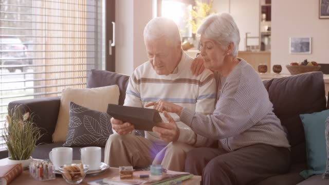 ds senior couple using a digital tablet on the sofa - senior couple stock videos & royalty-free footage