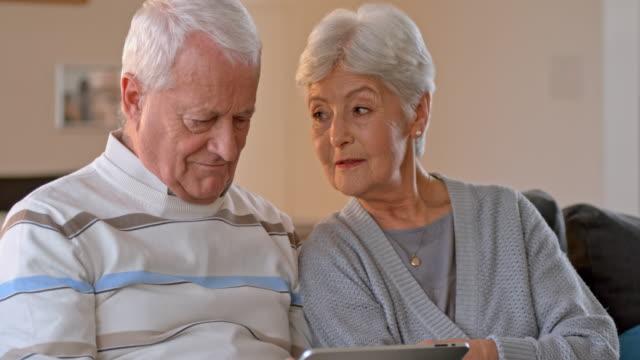 slo-mo-senior-paar mit einem digitalen tablet - seniorenpaar stock-videos und b-roll-filmmaterial