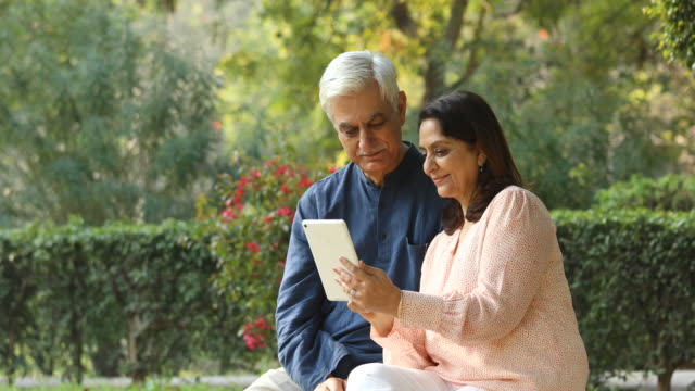 senior couple using digital tablet at park - indian ethnicity stock videos & royalty-free footage