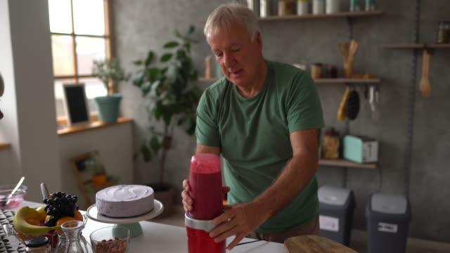 senior couple using electric juicer to make smoothie at home - electric juicer stock videos & royalty-free footage