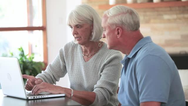 Senior couple using laptop and talking