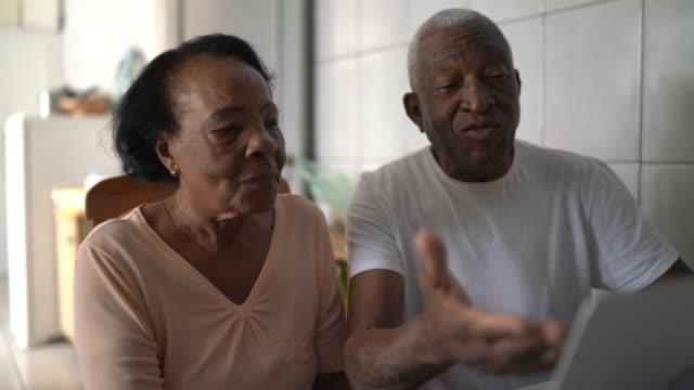 senior couple using laptop at kitchen - electronic banking stock videos & royalty-free footage