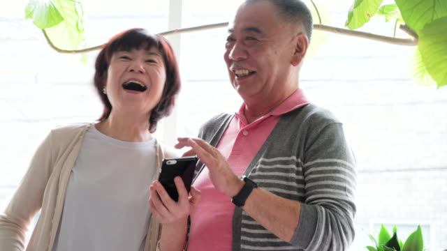 senior couple using smart phone - married stock videos & royalty-free footage