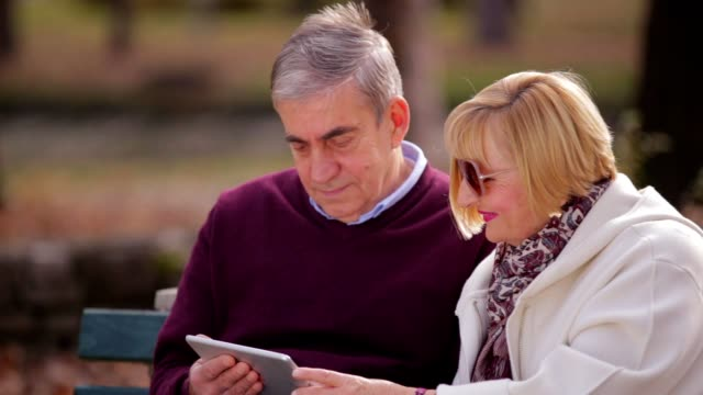 senior couple using tablet in the park - coppia di età matura video stock e b–roll